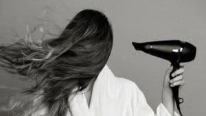 mujer morena secándose el pelo