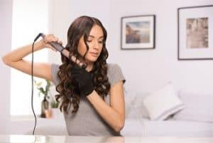 chica utilizando un rizador de pelo cónico
