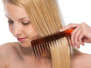 mujer rubia peinándose con peine de púas