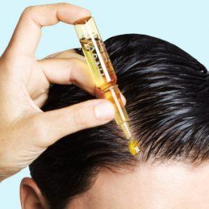 aplicando ampolla en un pelo negro liso